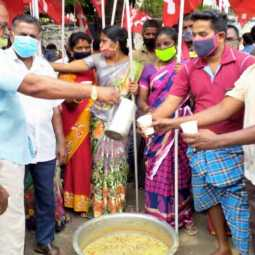 Heavy lifting workers in Trichy open a porridge tank with their families