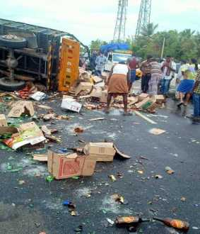 truck carrying liquor met with an accident and people taking away the liquor bottles